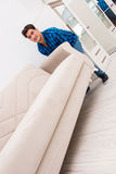 The young man moving sofa couch Stock Image