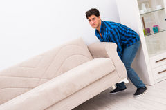 The young man moving sofa couch Royalty Free Stock Images