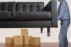 Young man is moving sofa. Moving to a new house concept. stock images