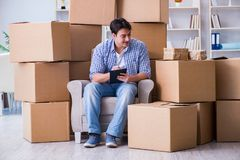 The young man moving in to new house with boxes Stock Photography