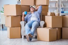 The young man moving in to new house with boxes. Young man moving in to new house with boxes Royalty Free Stock Images