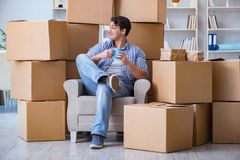 The young man moving in to new house with boxes. Young man moving in to new house with boxes Royalty Free Stock Photos