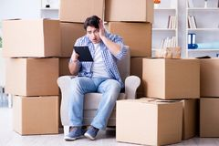 The young man moving in to new house with boxes. Young man moving in to new house with boxes Stock Images