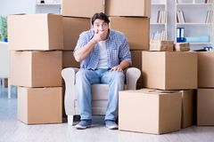 The young man moving in to new house with boxes. Young man moving in to new house with boxes Royalty Free Stock Image