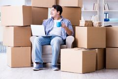 The young man moving in to new house with boxes Stock Images