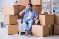 The young man moving in to new house with boxes. Young man moving in to new house with boxes Stock Photos
