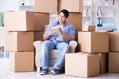 The young man moving in to new house with boxes. Young man moving in to new house with boxes Stock Image