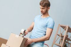 Young man moving to new place standing holding scotch tape packing box smiling thinking royalty free stock images