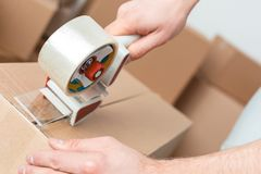 Young man moving to new place standing packing boxes with scotch tape close-up stock images