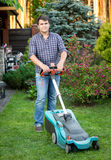 Young man mowing grass at house backyard Stock Photos