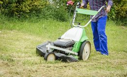 Young man mowing the lawn with a lawnmower Royalty Free Stock Photography