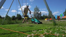 Young man mows the lawn with in children playground. Gimbal motion stock footage
