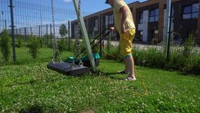 Young man mows lawn with electrical mower in children playground. Gimbal motion. Young man mowing lawn with electrical lawnmower in children playground stock video footage