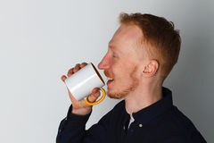 A young man with a mug of tea or coffee. He pleased. White background. Redhead male with white mug. Stock Photos