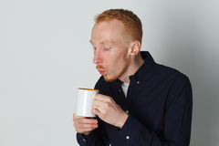 A young man with a mug of tea or coffee. He pleased. White background. Redhead male with white mug. Royalty Free Stock Images