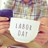 Young man with a mug with the text labor day Stock Image