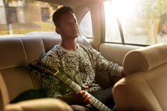 Young man multi race sitting on the back seat in the car. A singer holding a guitar while traveling inside of taxi. royalty free stock image