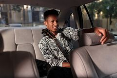 A happy man of mixed race, goes in the car, holding a guitar, with good mood, indoors image of car. royalty free stock photography