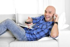Young man multi tasking working on laptop, phone and remote. Happy young latin man lying on sofa working on computer , talking on phone , changing channel with Royalty Free Stock Photo