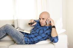 Young man multi tasking working on laptop, phone and remote Royalty Free Stock Image