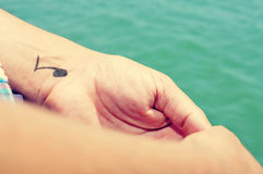 A young man with a musical note tattooed in his wrist. Closeup of a young caucasian man with some musical note tattooed in his wrist, chilling out on the sea Royalty Free Stock Images
