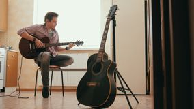Young man musician composes music on the guitar and plays in the kitchen, other musical instrument in the foreground,. Young man musician composes music on the stock video