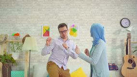Young man and muslim woman in hijab dancing fun
