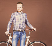 A young man with mustache and beard is near fashionable modern fixgear bicycle. Jeans and plaid shirt hipster style. Toned color Stock Photo