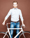 A young man with mustache and beard is near fashionable modern fixgear bicycle. Jeans and shirt, the bow tie hipster style. Toned Stock Photos