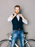 A young man with mustache and beard is near fashionable modern fixgear bicycle. Jeans and shirt, vest and straightens the bow tie Stock Images