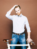 A young man with mustache and beard is near fashionable modern fixgear bicycle. Smooth hair on the head. Jeans and shirt, the bow Stock Photo