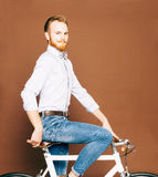 A young man with mustache and beard is sitting on a fashionable modern fixgear bicycle. Jeans and shirt, the bow tie hipster style Royalty Free Stock Photography
