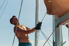 Young man with naked body setting sail on a sailing boat. stock photo