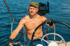 Young man with naked body steers the sailing boat. Royalty Free Stock Image