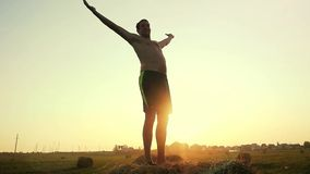 Young man with naked torso raises his hands in a field in slowmotion standing on the haystack during a beautiful sunset stock footage