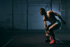 Young man with naked torso working out in gym. Young muscular man with naked torso working out in gym. Athletic male adult exercising with kettle bell. Fitness Stock Images
