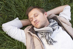 Young man napping alone on grass Stock Images
