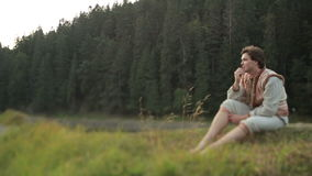 Young man in national ukrainian costume thoughtfully looks away. Breathtaking landscape of Carpathian mountains on stock footage