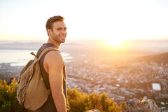 Young man on nature trail with a view of city. Smiling young man standing on a nature trail with a view of the city in the early morning stock photography