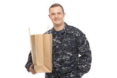 Young man in navy uniform with grocery store paper bag Stock Photos