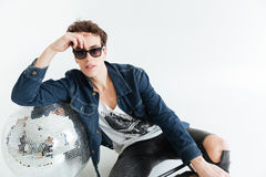 Young man near disco ball and boombox. Image of attractive young man wearing sunglasses sitting  over white background near disco ball and boombox. Looking at Stock Photos