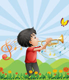 A young man near the hill playing with the trumpet Stock Photography