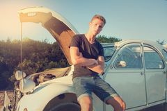 Young man near a Broken car. Young man near his broken car waiting for help Royalty Free Stock Images