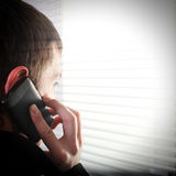 Young Man near Jalousie. Young Man see through the Jalousie and talking on Cellphone Royalty Free Stock Image