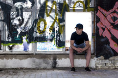 Young man near an old broken window. Young man sitting near an old broken window Royalty Free Stock Photography