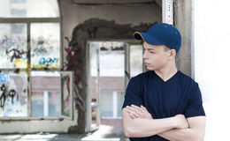 Young man near an old broken window. Young man stands near an old broken window Stock Image