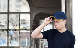 Young man near an old broken window. Young man stands near an old broken window Stock Photography