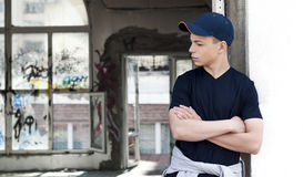 Young man near an old broken window. Young man stands near an old broken window Royalty Free Stock Image