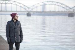 Young man near the river. Young hipster with moustache and beard in Riga Royalty Free Stock Photos