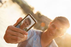 Young Man Near River Taking Selfie. Young Male Near River Taking Selfie Using Smart Phone Royalty Free Stock Photos